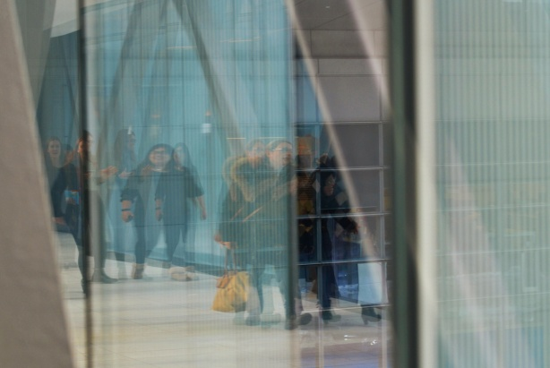 reflections of people walking in glass walled elevated walkway om downtown Toronto