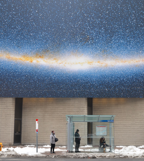 three people at a bus shelter waiting for a bis, two are standing and one is sitting. They are underneath a large photo of stars and the night sky