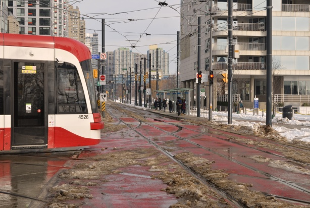 new TTC streetcar turning left from Spadina to Queens Quay, slushy streets after snowfall, people waiting at bus stop,