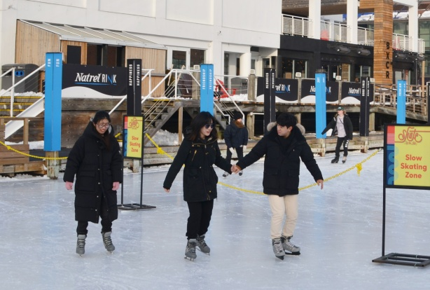 three people skating at an outdoor skating rink