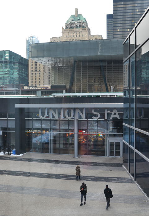 Union Station entrance, a couple of people walking in front, Royal York hotel in the background, taken from elevated walkway beside Scotiabank arena