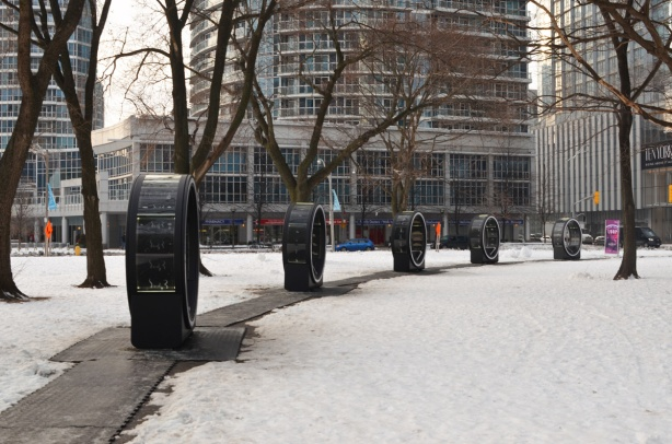 black circular structures that are part of an interactive art installation called Loop, arranged in a semi-circle at Yor Street Park, snow on the ground, trees with no leaves, no people there