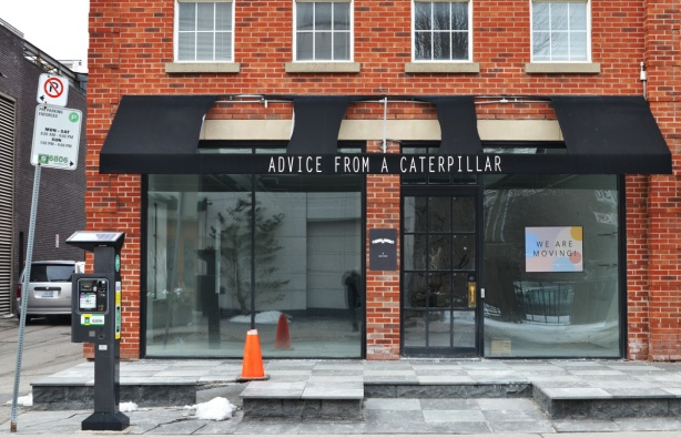 an empty storefront in a red brick building, black awning in front, words on awning say Advice from a caterpillar