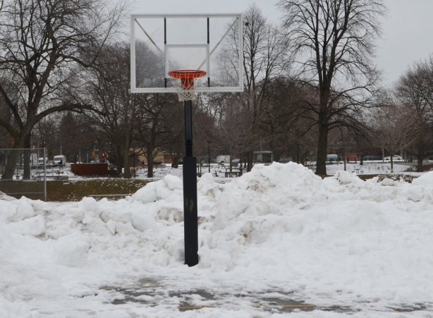 a basketball hoop on a metal pole in the snow in the park