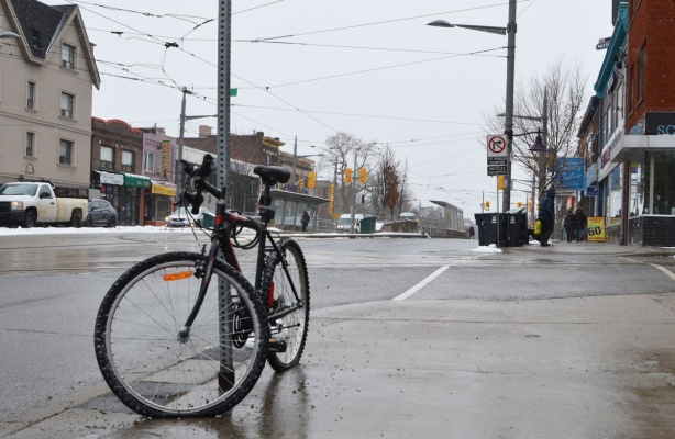 a bike with a flat front tire is locked to a street sign pole on the sidewalk on St. Clair west
