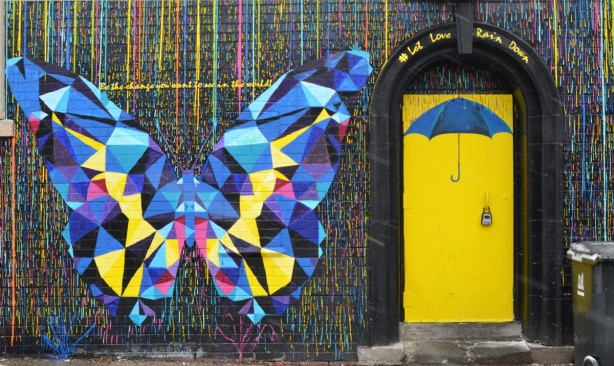 a multi coloured butterfly, mostly blue and yellow, made of geometric shapes, in a mural beside a yellow door with a blue umbrella painted on it