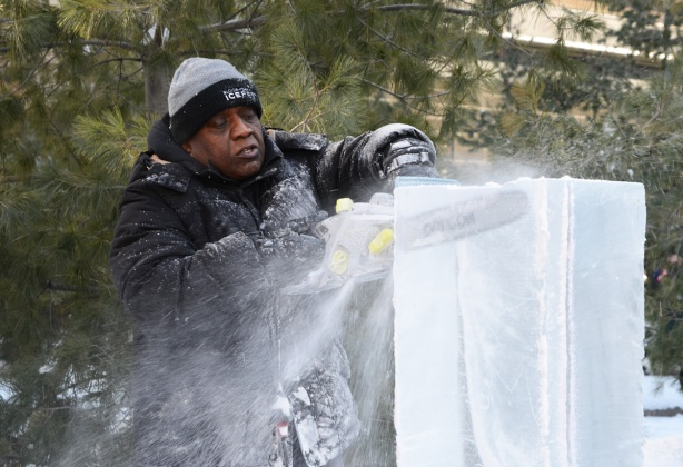 a man using a chainsaw to cut an ice block, bits of ice and snow flying away from the chainsaw