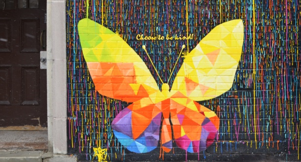 a butterfly in a colourful mural with the wods choose to be kind written above it