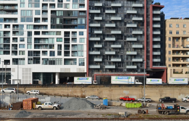 a line of glass and concrete condos on Front street that face the railway tracks, cars and trucks at construction site beside the tracks, below street level
