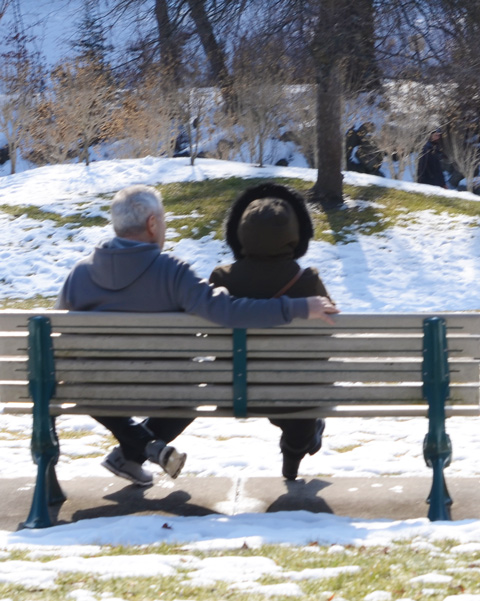 a couple sits on a bench, from behind, in winter clothes, snow on the ground in the park