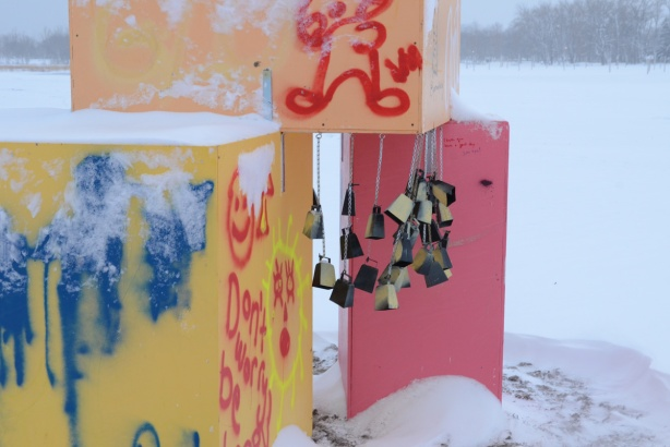 smal cowbells hang from the underside of a yellow box that is stacked on top of two other boxes, one yellow and one pink