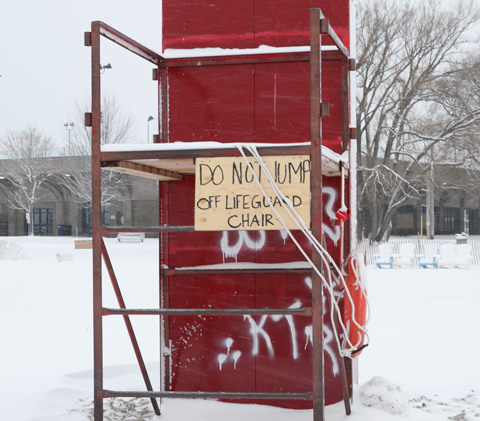 a metal frame lifeguard station, raised seat, with a red board against the back and a sign on the front that says do not jump off lifeguard chair
