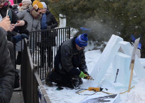 using an electric drill make a hole in a block of ice, outside, kneeling on the ground, ice fest, people watching the artist at work