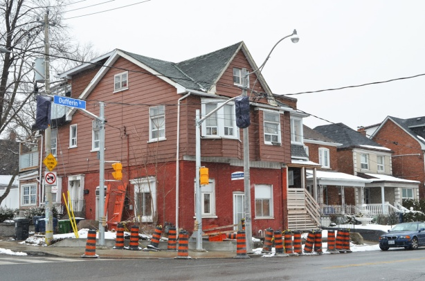 large house on the north west corner of Dufferin and Rosemount. Brick on the bottom, brown siding on the top, construction cones on the sidewalk around it