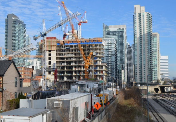 looking east along the north side of the railway tracks from Portland Street towards downtown, cranes and construction site, high rises