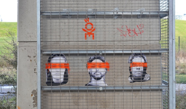 graffiti, three black and white photos of faces with orange streak painted through their eyes, pasteups on concrete
