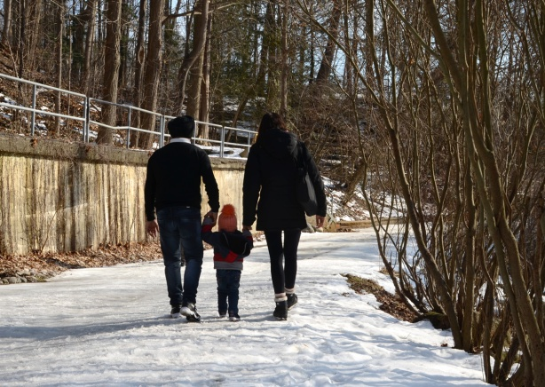 a family of three, mom, dad, and toddler, walking on snowy path at Wilket Creek, with toddler in middle