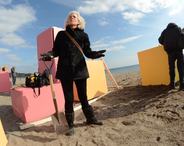woman holding a shovel, on beach, by some yellow and pink boxes, installing a public art display at Woodbine Beach