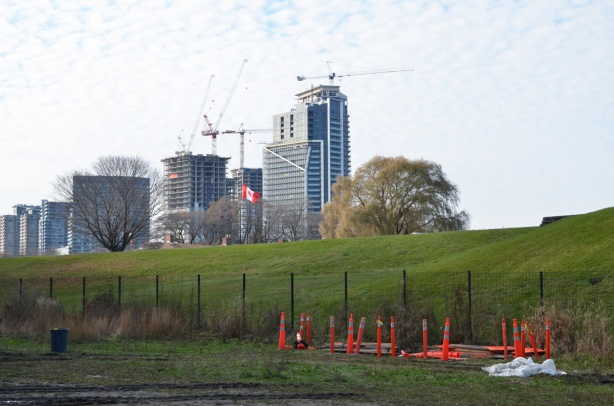 edge of the grounds of fort york, green grass on hill, with new high risse condos in the distance
