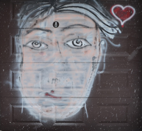 rough painting on a garage door of a man's face with a small red heart beside it