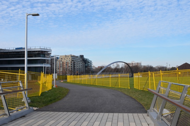yellow construction fences line the pathway through the middle of Garrison Crossing as it is not quite finished construction