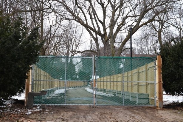fence and gate blocking a walkway through a park, construction zone now