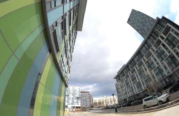 fish eye lens view of side of green library condo building and the other across the street, Queens Wharf Rd