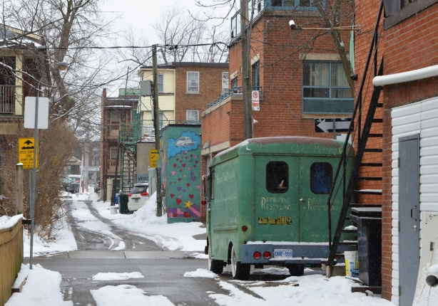 old green Chevrolet delivry van parked in a snowy alley, also part of a mural with hearts on it, alley scene