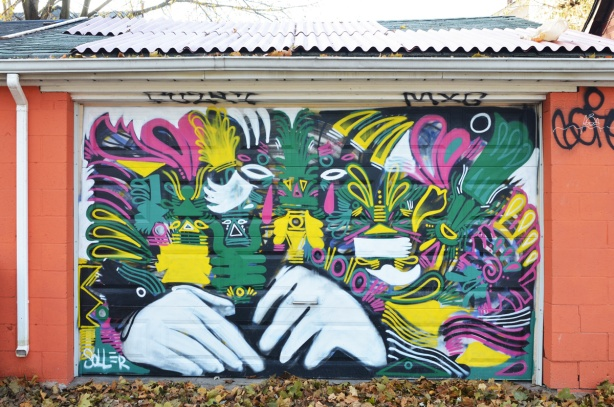 street art on a garage door including a large pair of white hands