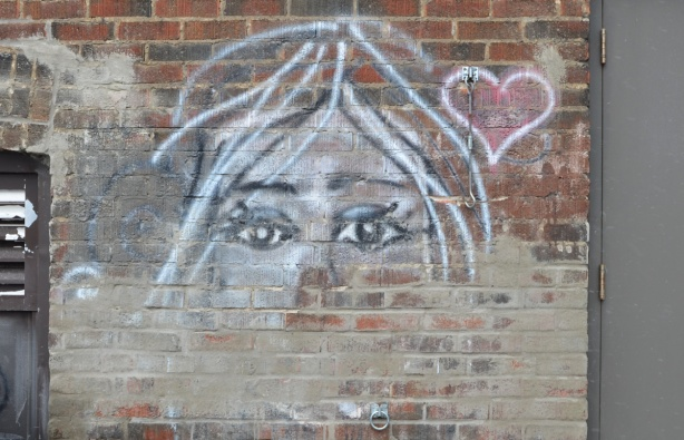 on a brick wall, a drawing of a woman's face with the eyes being the most prominent, a small red heart beside her face