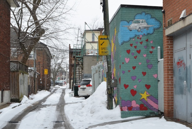 laneway scene, snow, car, poles, trees, garages, part of a mural with hearts on it