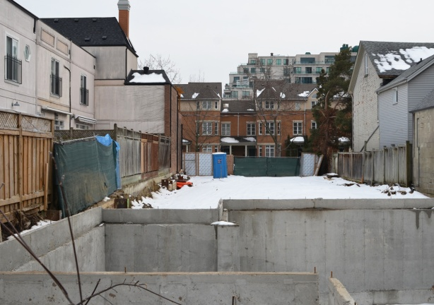 snow covered vacant lot with a concrete hole in the foreground, basement for a new house