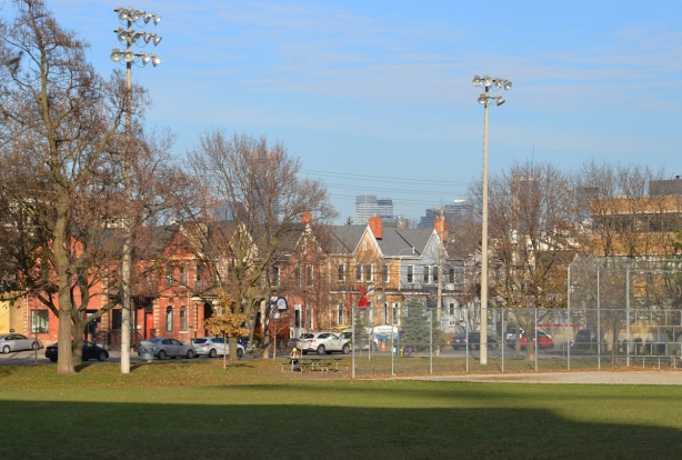 park, green space, baseball diamond with lights, and a row of bright coloured houses behind