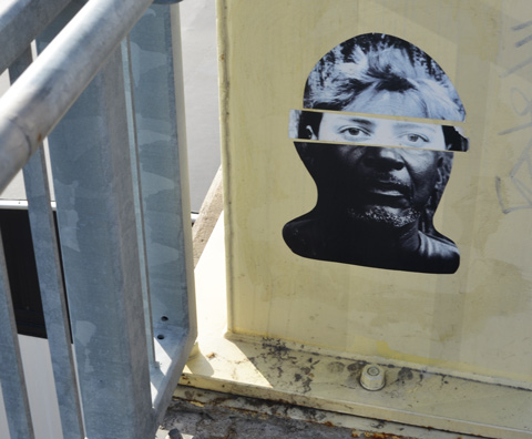 pasteup graffiti on a yellow post, faces with eyes collage, by jeremy lynch