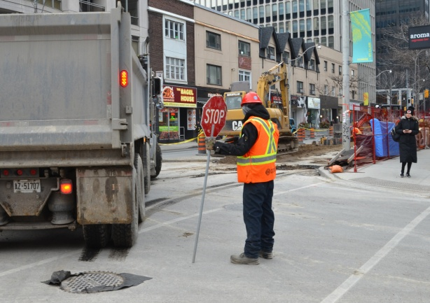 a workman holds a stop sign at an intersection while a dump truck backs up and makes a turn, construction zone on Yonge street