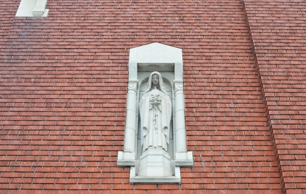 a small grey statue of Mary in a grey niche on the exterior of a brick church, St Mary of the Angels