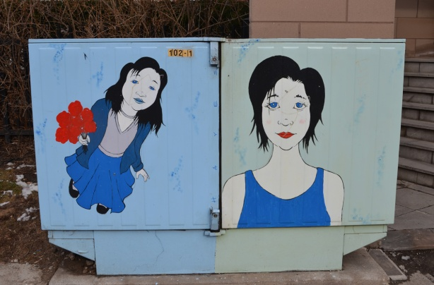 a metal box with two paintings of women, on the left, woman is holding a red flower in her hand