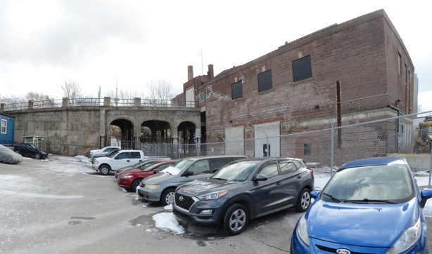 cars in a parking lot with an old boarded up brick building, 2 storeys. The building has a road and 3 arched bridge leading to the upper storey