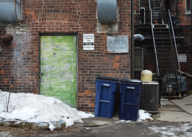 old beat up green door on the back of a brick building, lane, garbage bins there, also an old faded sign that says trespassers will be prosecuted, metal stairs leading up to upper storeys
