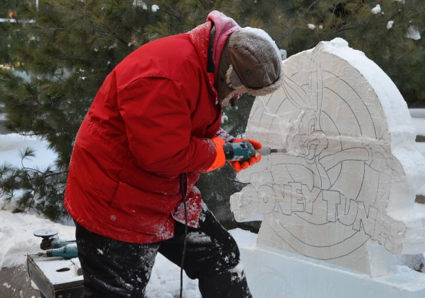 a man in a bright red winter jacket and brown hat and orange mitts is using a power drill to cut a picture of bugs bunny and the words looney tunes from a block of ice