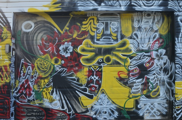 a garage door completely covered in paint, street art in red, black and yellow