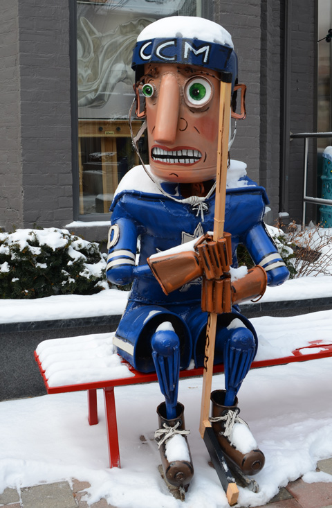 metal sculpture of a Toronto Maple Leaf hockey player sitting on a bench outside, holding his hockey stick and looking frightened, by Patrick Amiot
