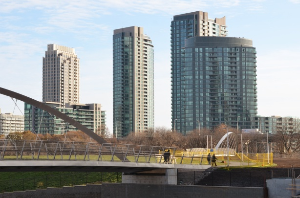 people walking across the Garrison Crossing bridge with high rise condos behind them