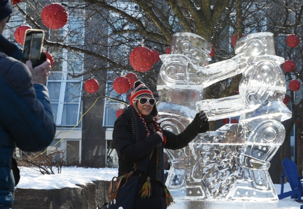a woman in a winter hat with the Union Jack on it, pointing at an ice sculpture while a man takes her picture