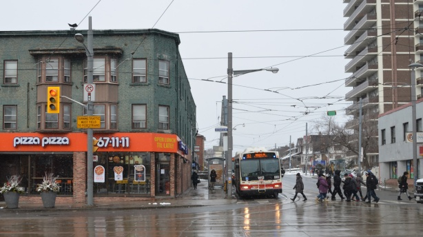 NW intersection of St. Clair and Oakwood with a bus at a bus stop and a pizza pizza restaurant