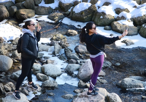 two women standing on the rocks in the creek at Wilket Creek park, taking selfies