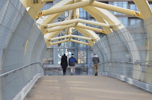 three people crossing the puente de luz, the yellow pedestrian bridge that crosses the railway tracks