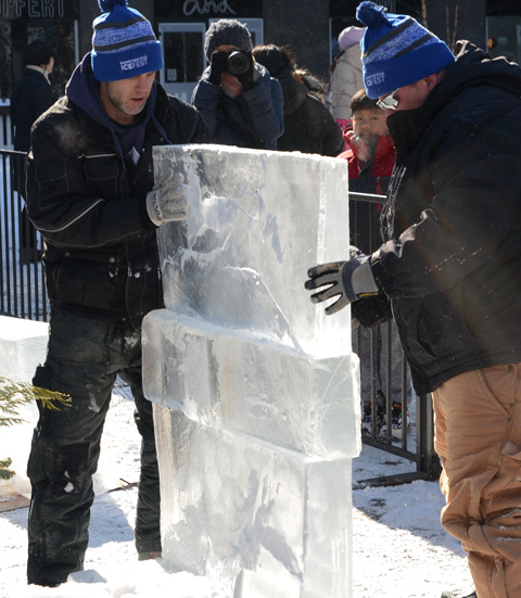 two men stacks slabs of ice together to make a small tower
