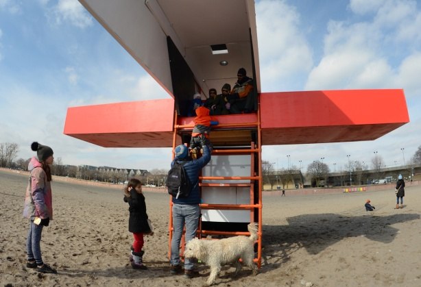 a father lifts up a young boy in a red winter coat so he can sit inside an art installation over a lifeguard station at the beach