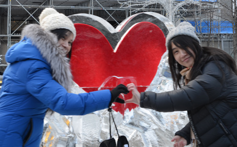 two women make a heart symbol with their hands in front of a red heart frozen inside an ice sculpture